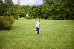 Ein nettes kleines Mädchen, das auf dem hellgrünen Gras läuft Lizenzfreie Stockbilder