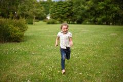 Ein nettes kleines Mädchen, das auf dem hellgrünen Gras läuft Stockfotos