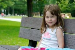 Nettes kleines Mädchen auf einer Bank Lizenzfreies Stockfoto