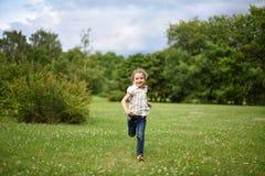 Ein nettes kleines Mädchen, das barfuß auf dem hellgrünen Gras läuft Lizenzfreies Stockbild