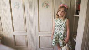 Ein nettes kleines Mädchen, das in einem Reinraum hält ein angefülltes Kaninchen steht stock video