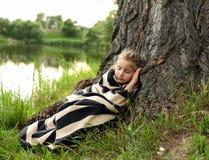 Ein nettes kleines Mädchen, das unter einem enormen Baum unter üppiger grüner Natur schläft Stockfotografie