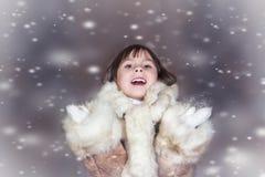 Ein nettes kleines Mädchen in einem Pelzmantel genießt Stockfoto