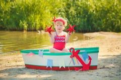 Ein nettes kleines Mädchen in einem roten Badeanzug, der auf dem Strand gegen den Hintergrund von Booten steht Stockfotos