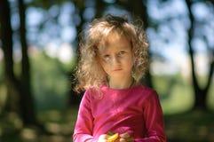 Ein nettes kleines Mädchen, ernster Blick, gelocktes Haar, sonniges Sommerporträt Lizenzfreies Stockfoto