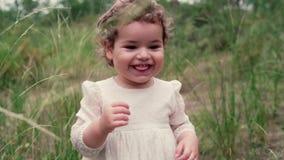 Ein nettes kleines Mädchen läuft herum in den Park Blondes Kind geht draußen kindheit stock video footage