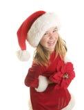 Ein nettes kleines Mädchen in Santa Claus Hat und in einem Kleid, die eine Poinsettia halten Lizenzfreies Stockfoto