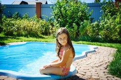 Ein nettes kleines Mädchen sitzt durch das Pool Stockfoto