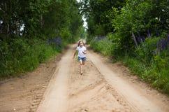 Ein nettes lächelndes kleines Mädchen, das barfuß in eine Landschaftslandschaft entlang einem Landweg läuft Lizenzfreies Stockbild