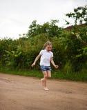 Ein nettes lächelndes kleines Mädchen, das barfuß in eine Landschaftslandschaft entlang einem Landweg läuft Lizenzfreie Stockfotos