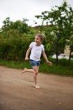 Ein nettes lächelndes kleines Mädchen, das barfuß in eine Landschaftslandschaft entlang einem Landweg läuft Stockfotografie