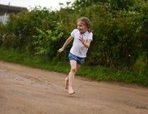 Ein nettes lächelndes kleines Mädchen, das barfuß in eine Landschaftslandschaft entlang einem Landweg läuft Lizenzfreies Stockfoto