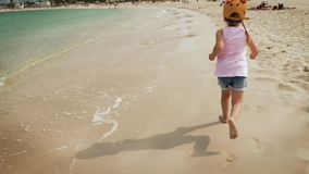 Ein nettes Mädchen, das entlang den Strand läuft stock video