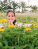 Ein nettes Mädchen legen sich auf einem Feld hin Lizenzfreies Stockbild