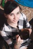 Ein nettes Mädchen mit einem Mikrofon, trinkender Kaffee, Stockbild