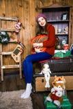 Ein nettes Mädchen sitzt in einem Raum mit hölzernen Wänden Neues Jahr und Chris Stockbild