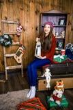 Ein nettes Mädchen sitzt in einem Raum mit hölzernen Wänden Neues Jahr und Chris Lizenzfreie Stockfotos