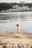 Ein nettes männliches Kind von drei Jahren laufend entlang den Strand nahe dem Wasser und Fliege spritzend Aktive Erholung im Som lizenzfreie stockfotografie