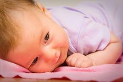 Ein nettes Schätzchen, das auf einem Bett lächelt Lizenzfreies Stockbild