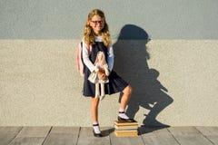 Ein nettes Schulmädchen der Grundschule lächelt mit einem Spielzeug in ihr Lizenzfreie Stockfotografie