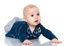 Ein nettes, sehr kleines Mädchen liegt auf dem Boden auf einem weißen backgr stockfotografie