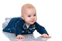 Ein nettes, sehr kleines Mädchen liegt auf dem Boden auf einem weißen backgr lizenzfreies stockbild