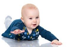 Ein nettes, sehr kleines Mädchen liegt auf dem Boden auf einem weißen backgr lizenzfreie stockfotografie