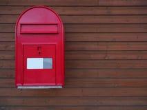 Ein neuer roter Briefkasten mit dunkelbraunem hölzernem Hintergrund Lizenzfreie Stockfotos