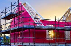 Ein neues Haus im Bau mit roter Schutzschicht, Baugerüst, Bauholz und hölzernen Brettern Stockbilder