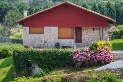 Ein neues Haus mit einem Garten in einem ländlichen Gebiet unter schönem Himmel Lizenzfreie Stockbilder
