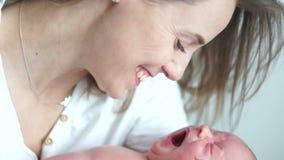 Ein neugeborenes Baby gähnt in den Armen seiner Mutter Mutter lächelt an ihrem Baby Sohn gibt der Mama eine Blume stock video footage