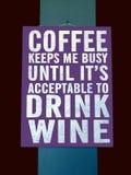 Ein Neuheitszeichen, das vorschlägt, dass Kaffee Sie beschäftigt bis seine Zeit, Wein zu trinken hält lizenzfreie stockfotografie