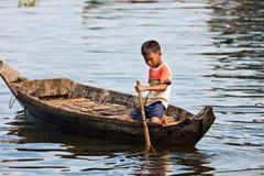 Ein nicht identifizierter Junge auf einem Boot, das auf Tonle Sap See schwimmt Lizenzfreies Stockfoto