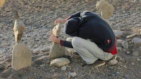 Ein nicht identifizierter Mann in einer Haube stellt Steinhaufen her Balance im Alltagsleben, Ruhe stock video