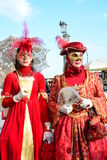 Ein nicht identifiziertes Paar von Frauen kleiden durchdachte rote Abendkleider mit Masken, weißen Handschuhen, Juwelen und Hüten Stockbild