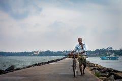 Ein nicht vertrauter älterer Mann trägt ein Fahrrad entlang der Küste des Ozeans stockbilder