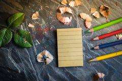Ein Notizbuch für Anmerkungen mit Zeichenstiften und Bleistiften Bleistiftspitzer gesetzt auf eine Tabelle gemacht vom Stein Unte Stockbilder