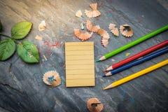 Ein Notizbuch für Anmerkungen mit Zeichenstiften und Bleistiften Bleistiftspitzer gesetzt auf eine Tabelle gemacht vom Stein Unte Stockfoto