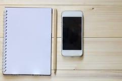 Ein Notizbuch mit einem Bleistift und einem intelligenten Telefon auf hölzernem backgroun stockbilder