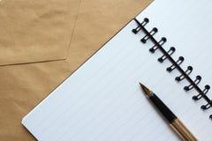 Ein Notizbuch mit leeren Blättern, einem Umschlag und einem Goldstift auf dem Tisch stockfotografie