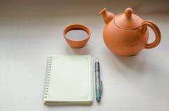 Ein Notizbuch und ein teaset stockbilder