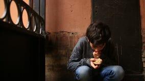 Ein obdachloser Jugendlicher, der eine Kruste des Brotes in einem Zugang vor dem hintergrund eines Gitters isst stock footage