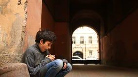 Ein obdachloser Jugendlicher, der eine Kruste des Brotes in einem Zugang vor dem hintergrund eines Gitters isst stock video footage