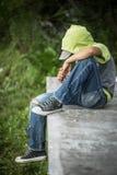 Ein obdachloser Junge sitzt auf einer Bank mit ihrem Kopf, der unten gebeugt wird Lizenzfreies Stockbild