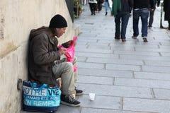 Ein obdachloser Mann, der auf der Straße sitzt Stockfoto