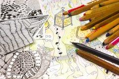 Ein obenliegendes Foto einiger alter benutzter schmutziger Bleistifte und abstrakter Gekritzelmuster gemacht vom schwarzen Zwisch Lizenzfreie Stockfotografie