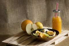 Ein Obstsalat, eine Flasche Mangosaft und einige Stücke frische Frucht lizenzfreie stockbilder
