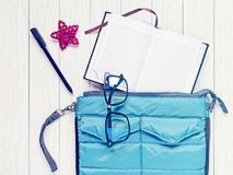 Ein offener Notizblock, eine blaue Ordnertasche, schwarz umrandete Brille, ein schwarzer Stift und ein roter Weidenstern sind auf Stockbild