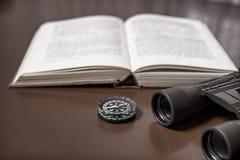 Ein offenes Buch auf dem Tisch, mit einem Paar von Ferngläsern und von Kompass Lizenzfreie Stockfotos