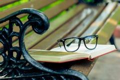 Ein offenes Buch und Gläser liegen am Rand einer Bank Lizenzfreie Stockfotos